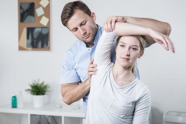 Physical therapist with a patient at a clinic.